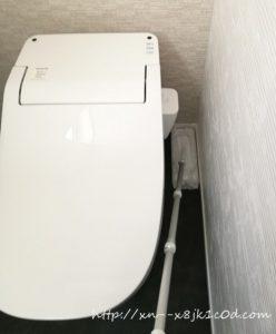トイレの床をクイックルワイパーで掃除中の写真